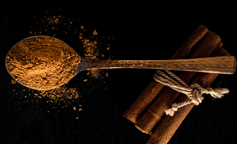ground cinnamon on spoon dark background